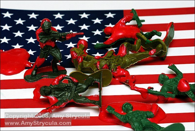 A conceptual photo depicting toy soliders in a pool of blood on an American Flag.