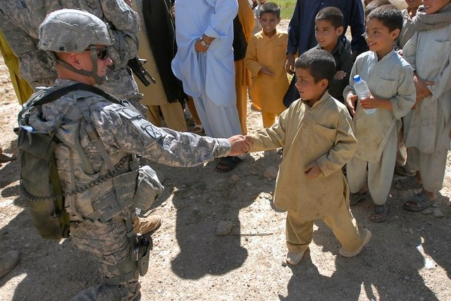 Army 1st Lt. Barry Klinger, Headquarters and Headquarters Troop, 3rd Squadron, 71st Cavalry Regiment, makes a friend while in the village of Altimur in Logar province, Afghanistan, June 20. Klinger and his Soldiers, along with Afghan National Policemen and Czech army Soldiers, visited the village to assess the local needs and warn them of upcoming artillery training operations they were scheduled to conduct in the area. (U.S. Army photo by Spc. Jaime' DeLeon, 3rd Brigade Combat Team, 10th Mountain Division, Public Affairs Office)