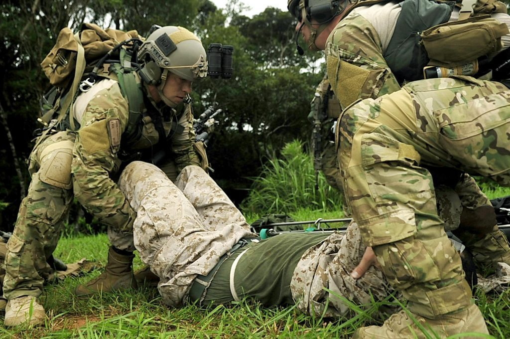 Senior Airmen Daniel Flechsenhaar (left) and Andrew Nichols move a simulated wounded Marine on to a litter during a joint combat training exercise July 28, 2010, at Kadena Air Base, Japan. The Airmen are pararescuemen from the 31st and 33rd Rescue Squadrons. (U.S. Air Force photo/Senior Airman Amanda N. Grabiec)